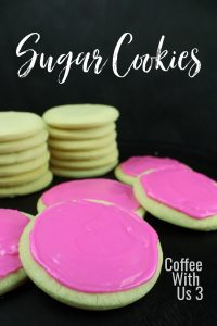 Pink frosted sugar cookies with two stacks of unfrosted cookies.
