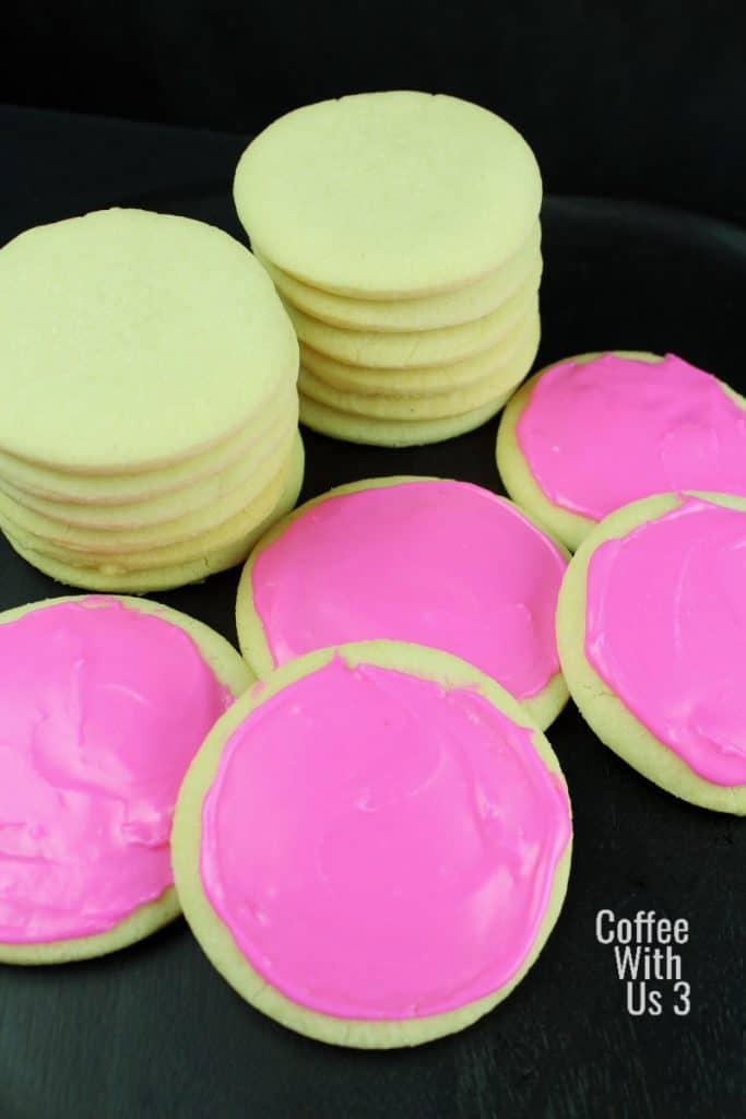 Sugar cookies frosted with pink icing and two stacks of unfrosted cookies