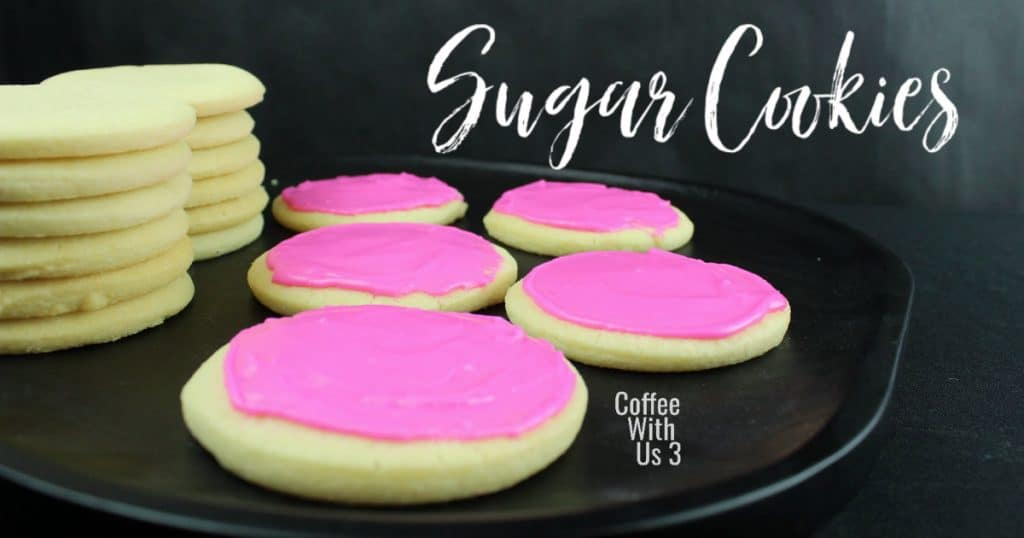 Pink frosted sugar cookies with two stacks of cookies in the background
