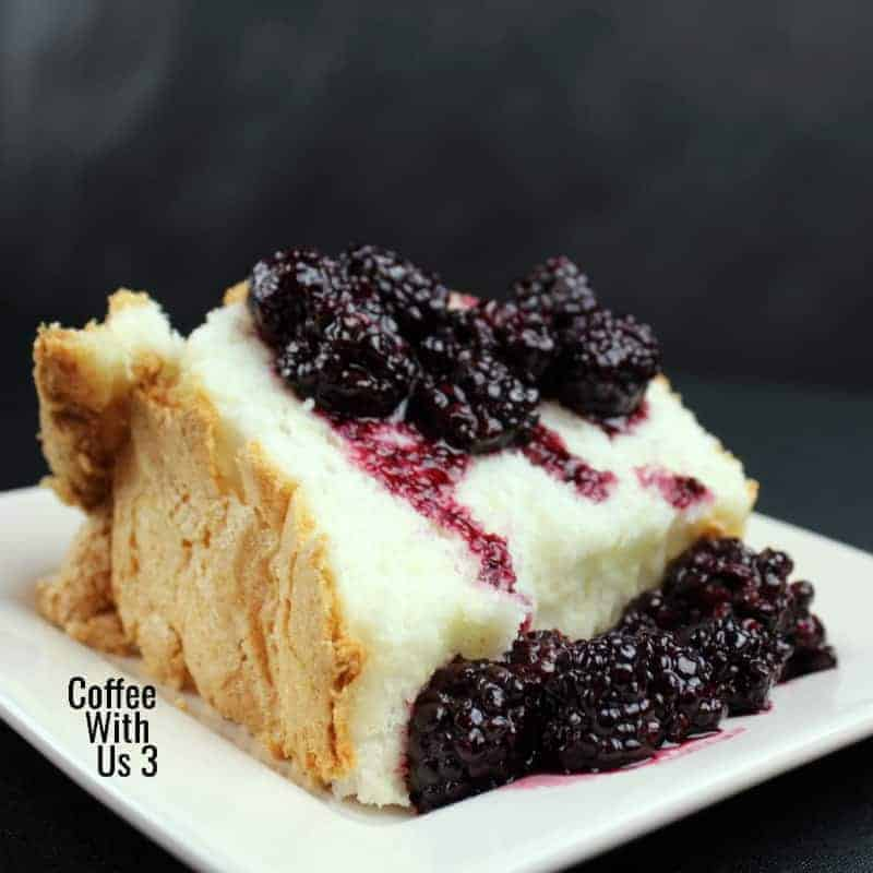Slice of angel food cake with blackberry topping on a white plate