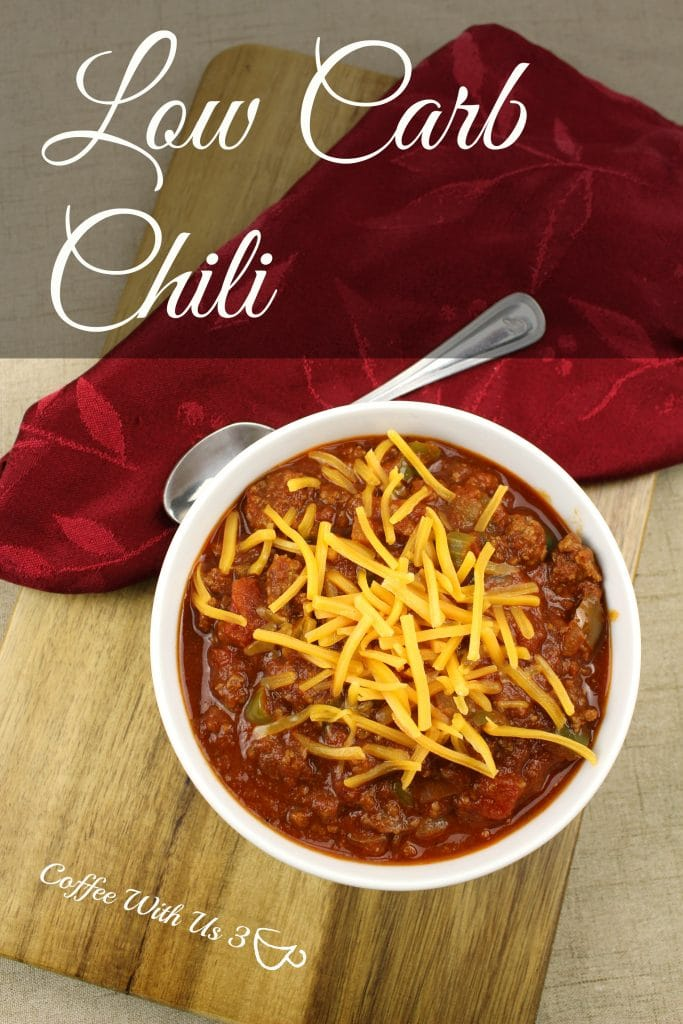 Low carb chili topped with cheese with spoon and napkin laying next to bowl.