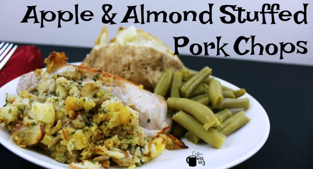 Apple and almond stuffed pork chops on a plate with baked potato and green beans.
