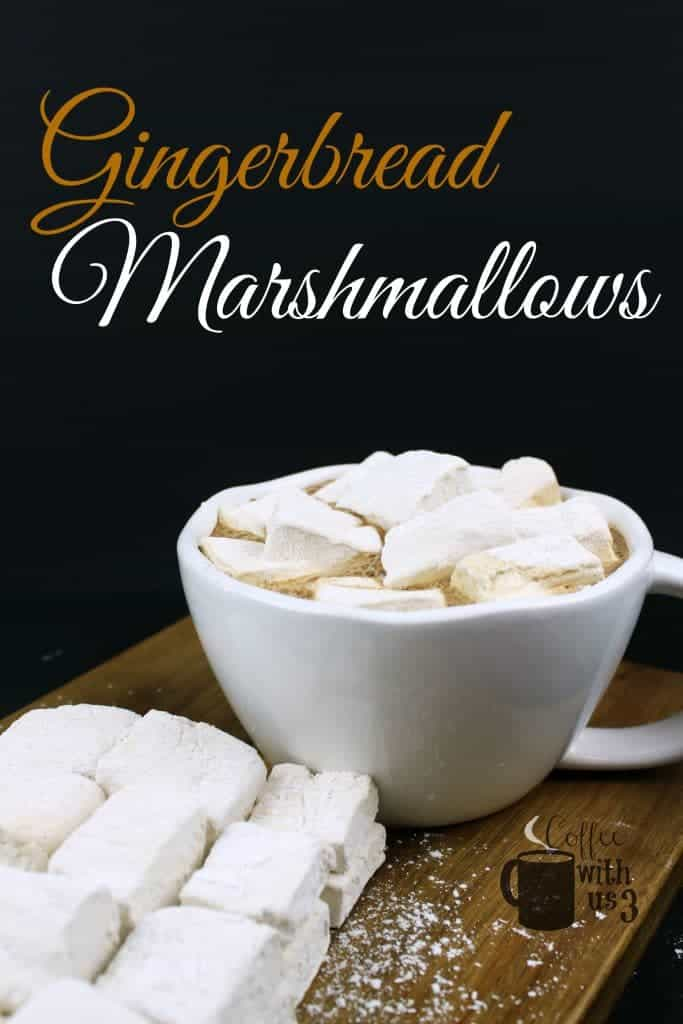 Gingerbread Marshmallows topping hot cocoa and marshmallows in front on a charcuterie board.