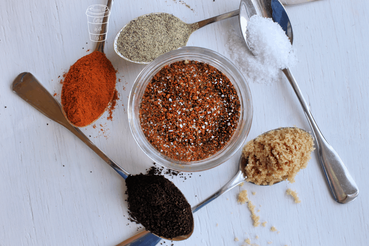 Spoons filled with ingredients surrounding a jar filled with coffee dry rub.